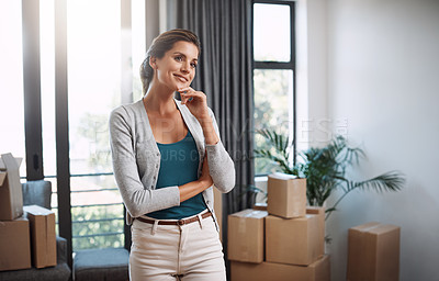 Buy stock photo Cropped shot of an attractive young woman looking thoughtful standing in her new home while moving in