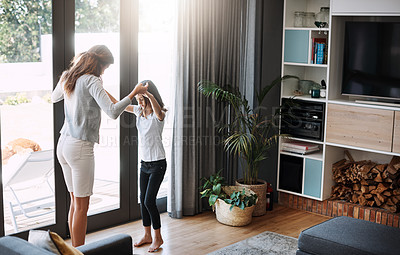 Buy stock photo Full length shot of an attractive young woman and her daughter dancing while spending time together at home