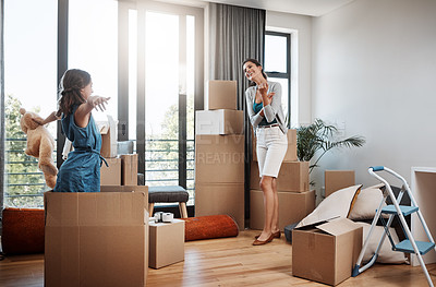 Buy stock photo Full length shot of an attractive young woman and her daughter moving into a new house