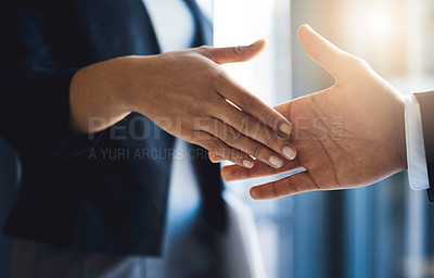 Buy stock photo Closeup shot of two unrecognizable businesspeople shaking hands in an office