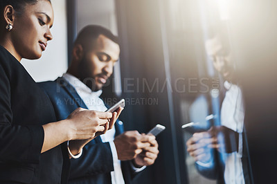 Buy stock photo Shot of two businesspeople using their cellphones in an office