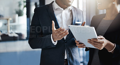 Buy stock photo Closeup shot of two unrecognizable businesspeople using a digital tablet together in an office