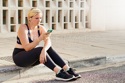 Buy stock photo Shot of an attractive young woman using a cellphone while working out in the city