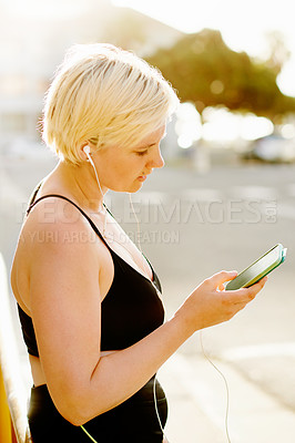 Buy stock photo Cropped shot of an attractive young woman using a cellphone while working out in the city