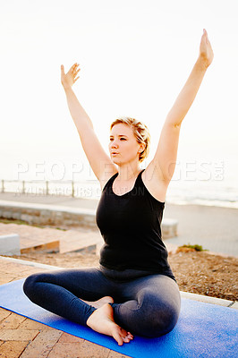 Buy stock photo Shot of an attractive young woman practising yoga on the promenade at the beach