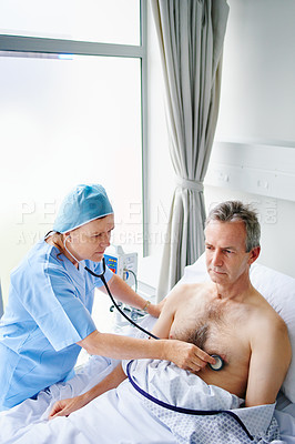 Buy stock photo High angle shot of a mature female doctor checking her male patient's heartbeat in his hospital bed