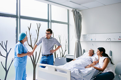 Buy stock photo Cropped shot of a handsome man talking to a female doctor while he and his wife visit his father in the hospital