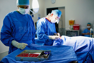 Buy stock photo Cropped shot of two doctors performing surgery in the operating room