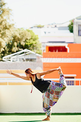 Buy stock photo Shot of a beautiful young woman practising yoga on a rooftop