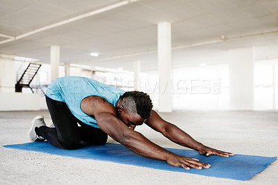 Buy stock photo Shot of a handsome and sporty young man doing yoga in an underground parking lot