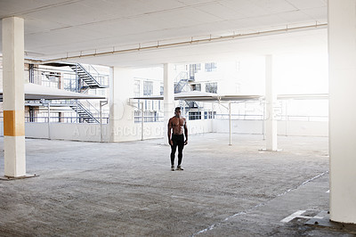 Buy stock photo Shot of a handsome and shirtless young man working out in an underground parking lot