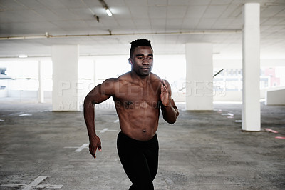 Buy stock photo Shot of a handsome and shirtless young man going for a run around the city