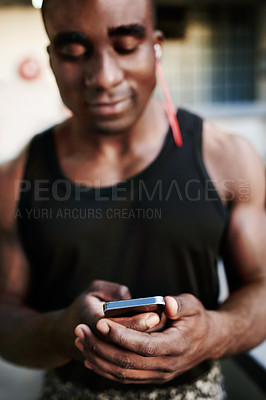 Buy stock photo Shot of a sporty young man using a mobile phone during his workout out in the city