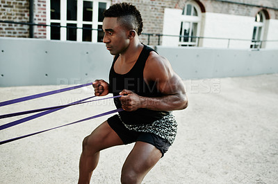 Buy stock photo Shot of a handsome and sporty young man working out with resistance bands in the city