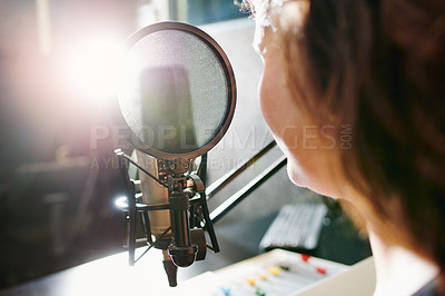Buy stock photo Shot of a woman speaking into a microphone in a recording studio