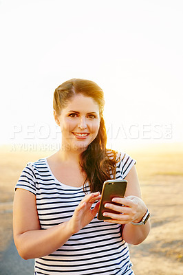 Buy stock photo Cropped shot of a beautiful young woman using a cellphone while spending the day on the promenade at the beach