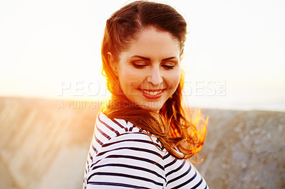 Buy stock photo Cropped shot of a beautiful young woman spending the day on the promenade at the beach