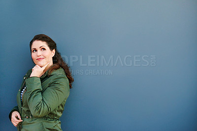 Buy stock photo Cropped shot of a beautiful young woman posing against a blue wall outside