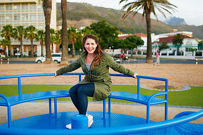 Buy stock photo Shot of a beautiful young woman having fun in a playground outside