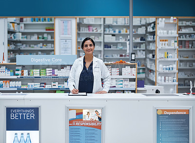 Buy stock photo Portrait of a mature pharmacist writing on a clipboard in a chemist
