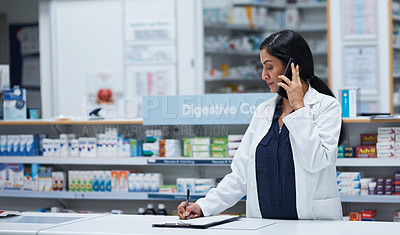 Buy stock photo Shot of a mature pharmacist talking on a cellphone while working in a pharmacy