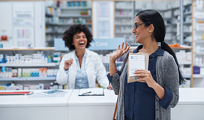 Buy stock photo Shot of a mature woman waving to a pharmacist in a chemist
