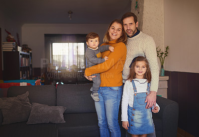Buy stock photo Cropped portrait of an affectionate young family of four standing in their living room at home