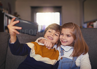 Buy stock photo Cropped shot of an adorable little boy and his older sister taking selfies while sitting on the sofa at home