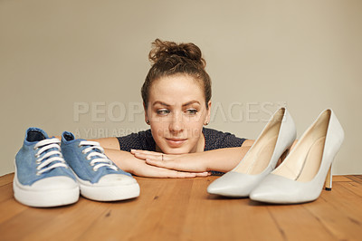 Buy stock photo Cropped shot of an attractive young woman deciding between two pairs very different shoes