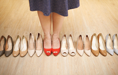 Buy stock photo High angle shot of an unrecognizable woman trying on high heels one by one as their lined up on a wooden floor