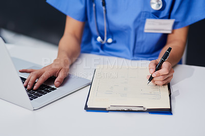 Buy stock photo High angle shot of an unrecognizable female nurse filling out paperwork while sitting at her desk in the hospital