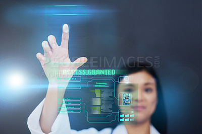 Buy stock photo Cropped shot of an attractive young female nurse using a touchscreen interface while standing against a black background