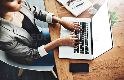 Buy stock photo High angle shot of an unrecognizable businesswoman working on a laptop in an office