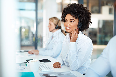 Buy stock photo Shot of a young call centre agent working alongside her colleagues in an office
