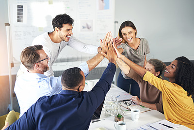 Buy stock photo Cropped shot of a group of businesspeople putting their hands in a huddle during a meeting in the boardroom