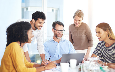 Buy stock photo Shot of a handsome mature businessman showing his colleagues information on his laptop during a meeting in the boardroom