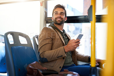 Buy stock photo Cropped shot of a handsome young man sending a text message during his morning bus commute