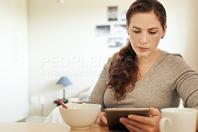 Buy stock photo Cropped shot of a beautiful young woman using a tablet while having breakfast in the kitchen at home