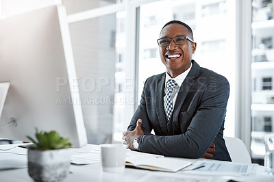 Buy stock photo Portrait of a young businessman working at his desk in a modern office