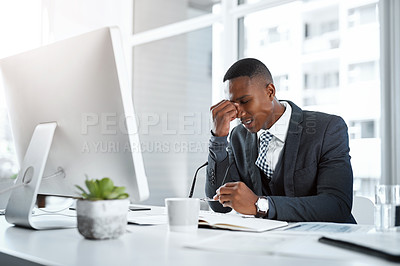 Buy stock photo Shot of a young businessman experiencing stress while working at his desk in a modern office
