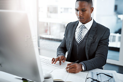 Buy stock photo Shot of a young businessman using a computer and writing notes at his desk in a modern office