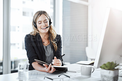 Buy stock photo Shot of a young woman using a headset and computer at her desk in a modern office