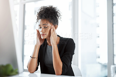 Buy stock photo Shot of a young businesswoman experiencing stress while working at her desk in a modern office