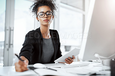 Buy stock photo Shot of a young businesswoman using a digital tablet, computer and writing notes at her desk in a modern office