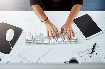 Buy stock photo Cropped sigh angle shot of a businesswoman using a computer at her desk in a modern office