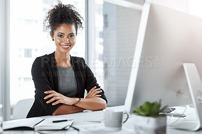 Buy stock photo Portrait of a young businesswoman working at her desk in a modern office