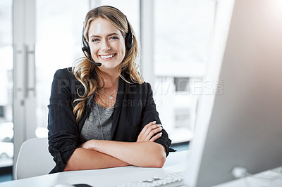 Buy stock photo Portrait of a young woman using a headset and computer at her desk in a modern office