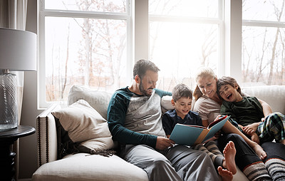 Buy stock photo Shot of two adorable brothers reading a book together with their parents while relaxing on the sofa at home