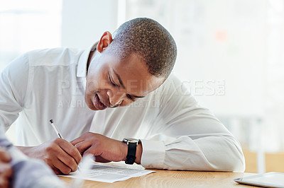 Buy stock photo Shot of a young businessman filling in paperwork in an office