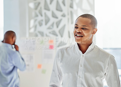 Buy stock photo Shot of a young businessman standing in an office with his colleague in the background